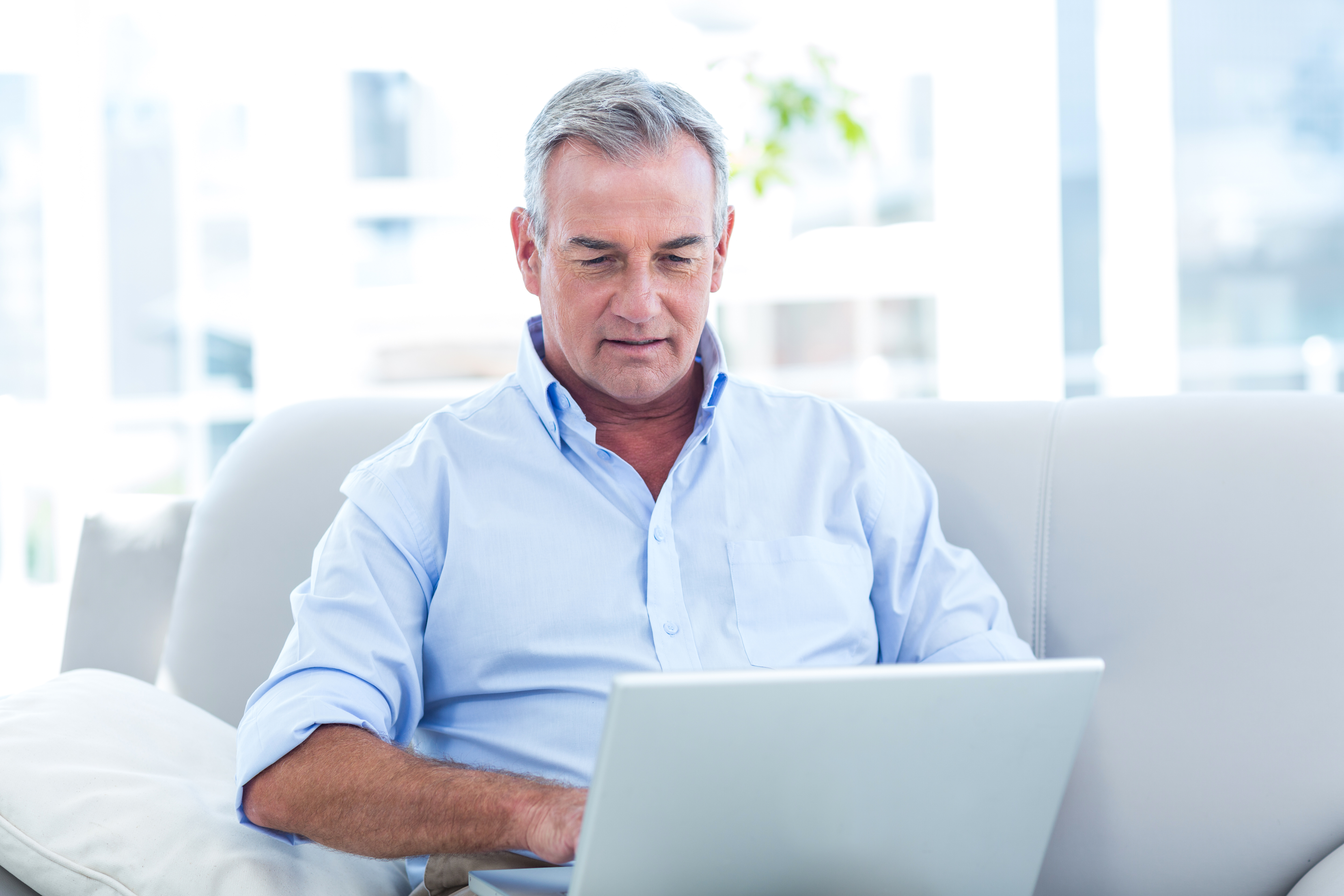 Man using laptop to learn about College Savings Accounts and Financial Aid