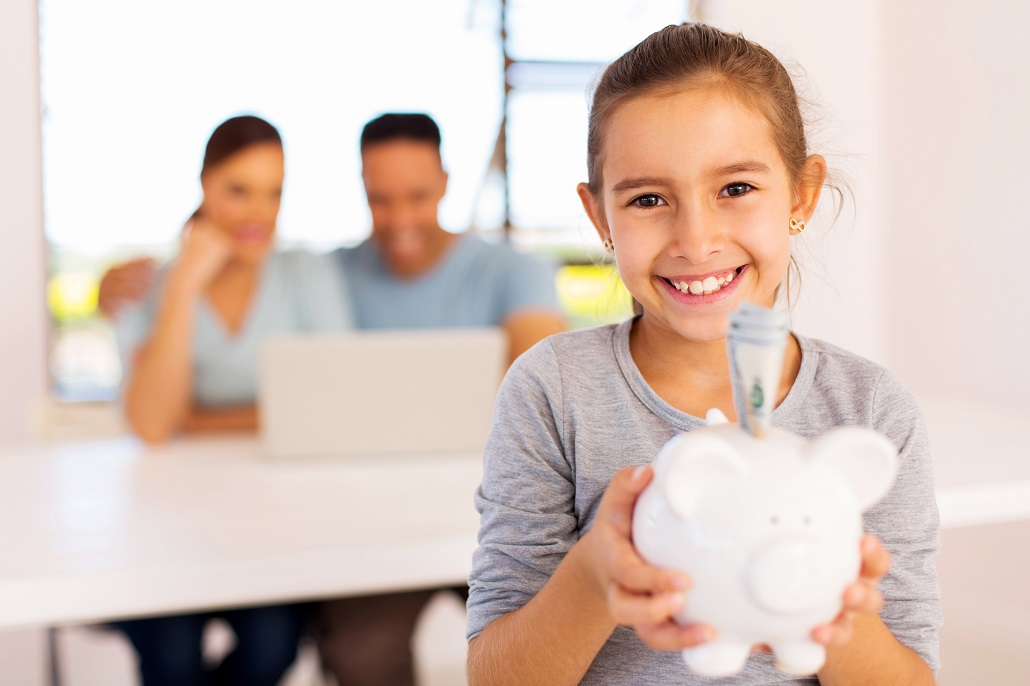 Young girl holding piggy bank