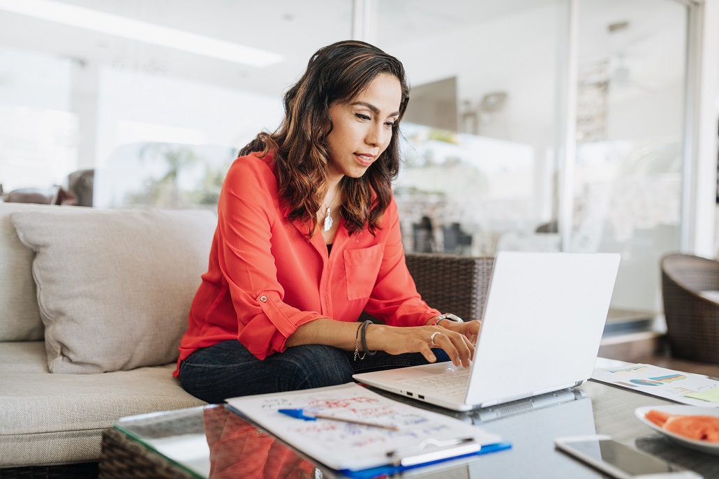 Woman using laptop to read FAQs about borrowing a loan