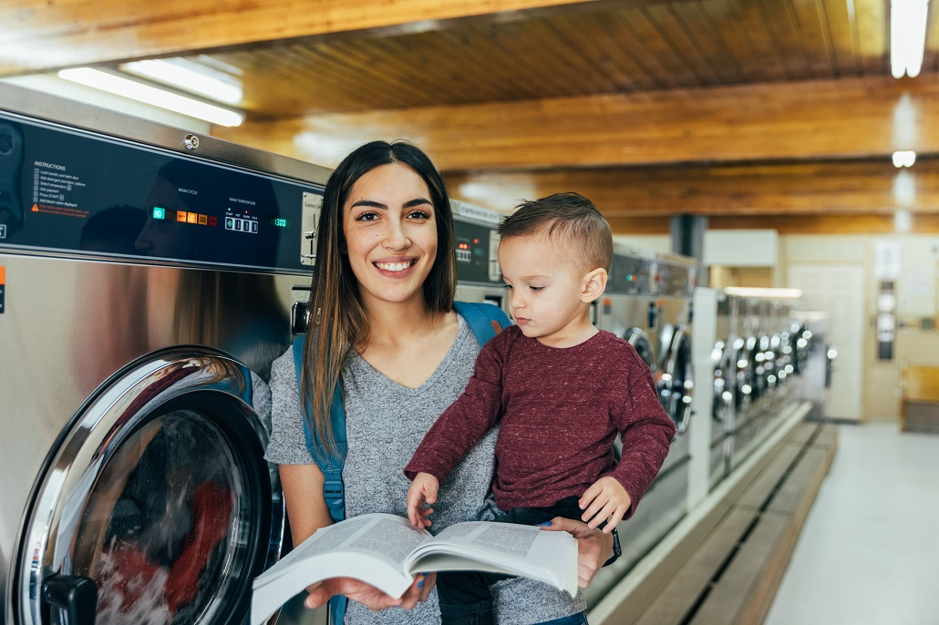 Woman holding son and reading book after returning to college as an adult