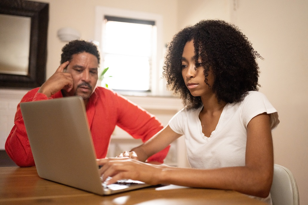 Father and daughter using computer to learn about MEFA Loans