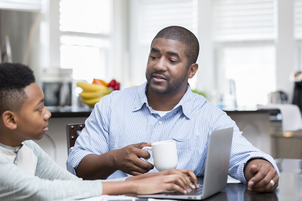 Father and son using computer to learn about saving for college