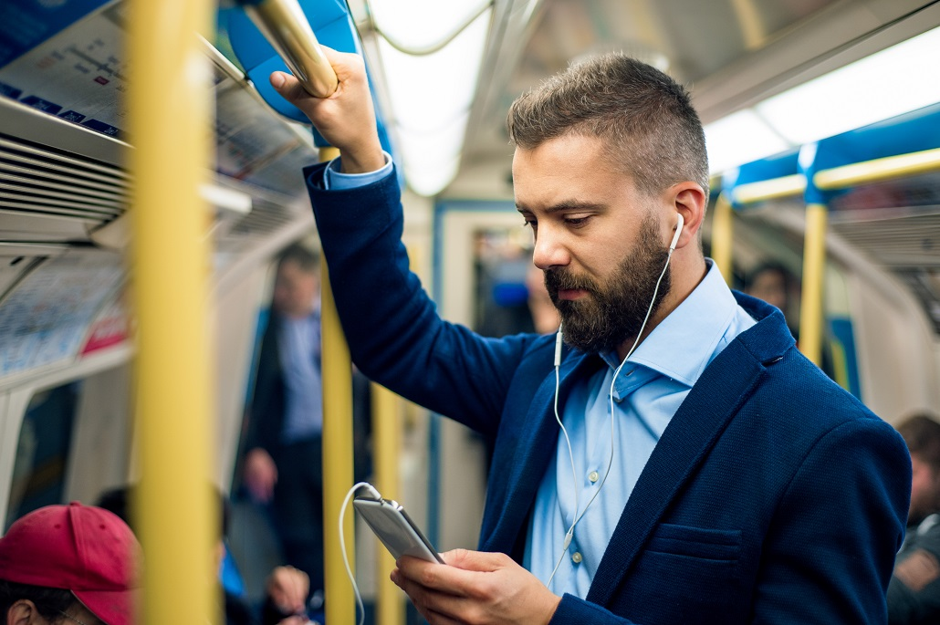 Man on train using his phone