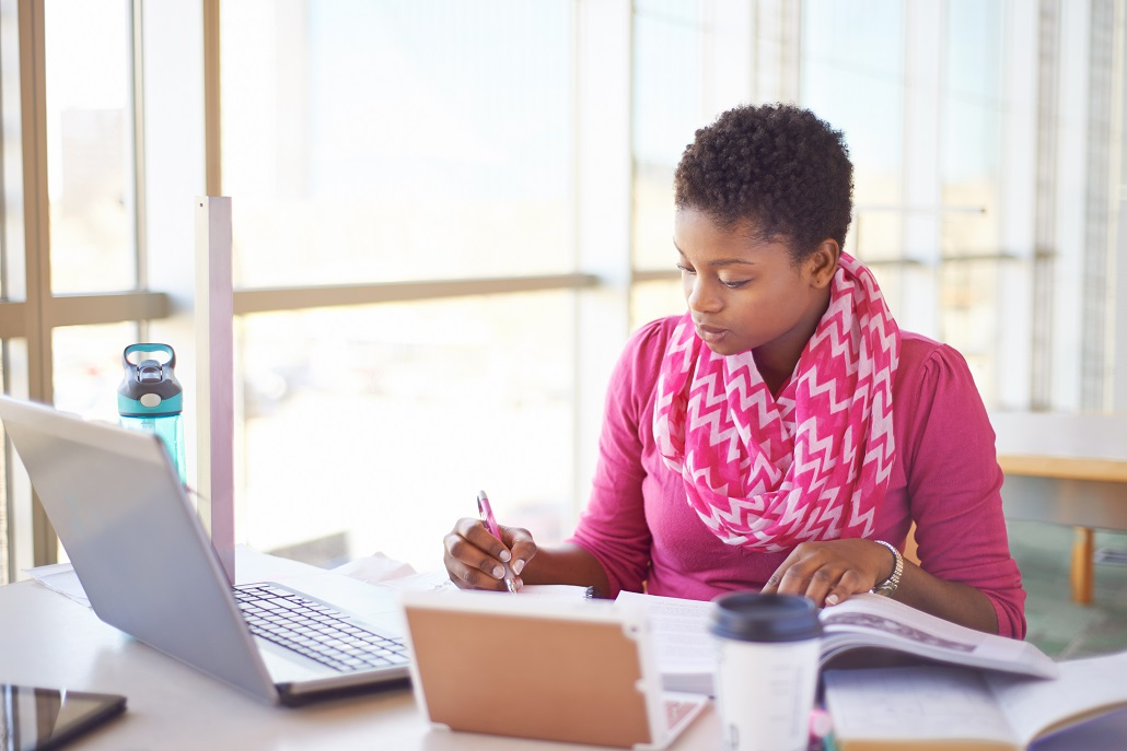 Woman using laptop to research how to pay for graduate school