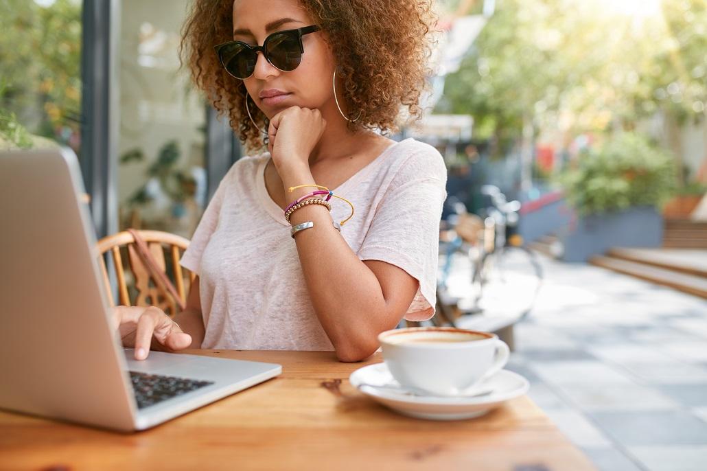 Girl using laptop at cafe