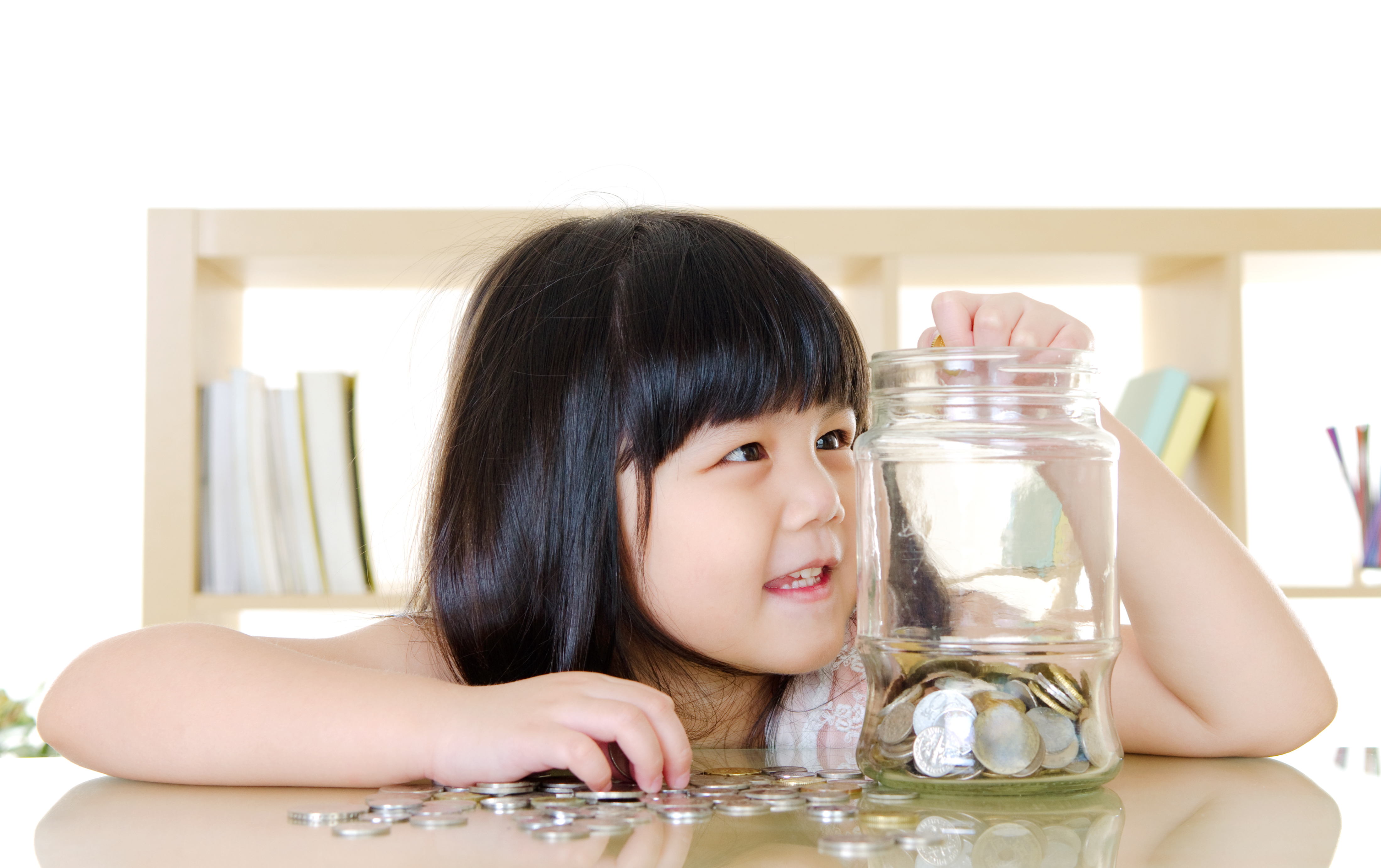 Young girl putting coins in a jar