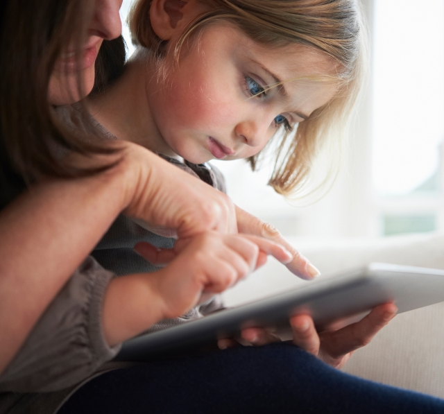Mother on a tablet with her young daughter
