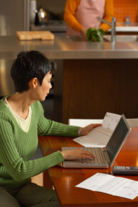 Woman with laptop computer paying bills at home