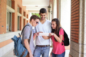 Happy College students using tablet pc on campus, caucasian