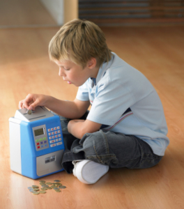 Boy sitting on floor putting coins in a piggy bank