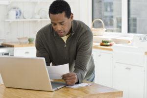 Man standing at laptop computer with paper documents