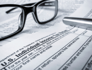 Glasses and pen sitting on a tax return