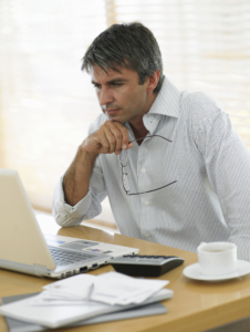 Man at desk, looking at laptop