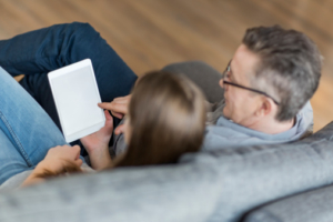Father and teenage daughter looking at a tablet seated on a couch