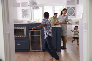 Parents with two children running in kitchen