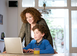 Mother overlooking middle school son working on laptop