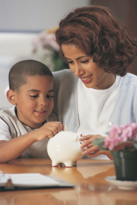 Mother and young son with piggy bank