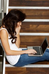 Teenage girl sitting on stairs with laptop