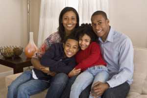 Two parents with two children sitting on a couch