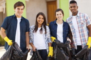 Four teenagers holding trash bags