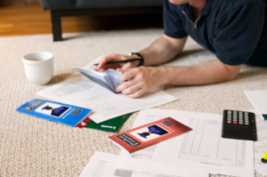 Man on ground with checkbook and paperwork