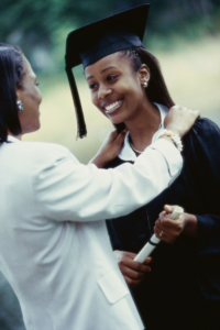 Woman standing with smiling female graduate