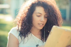 Teenage girl looking at a tablet outside