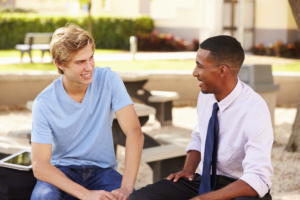 Counselor talking to high school student outside