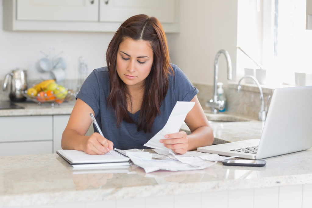 Woman calculating receipts with laptop