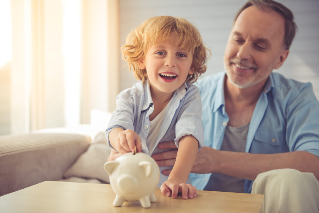 Young boy and grandfather saving money in piggy bank