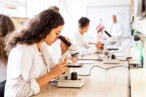 High school student using microscope