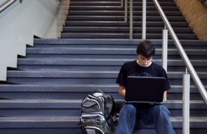 High school student using laptop on stairs