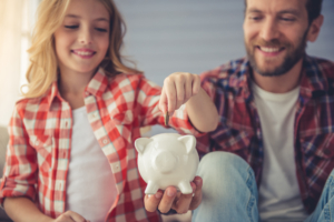 Father and daughter saving money in piggy bank