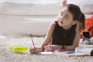 Young girl homework on floor