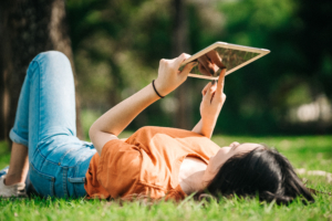 Woman laying in grass using tablet