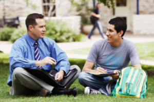 Counselor talking with student on the school lawn