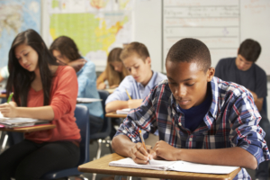 Student writing in a classroom