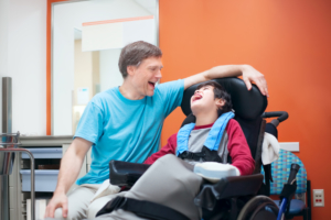Father laughing with son in wheelchair